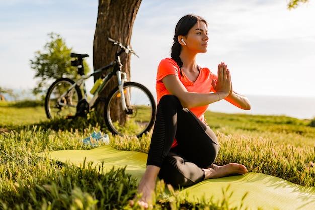 Schlanke schöne frau, die sport am morgen im park tut, der yoga tut