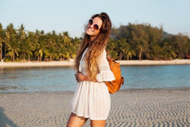 Schlanke schöne frau im weißen kleid am tropischen strand auf sonnenuntergang, der lederrucksack hält.