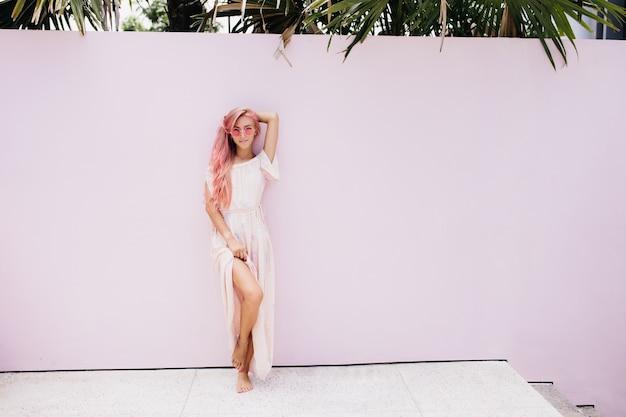 Schlanke schöne frau mit langen rosa haaren mit sanftem lächeln.