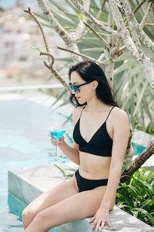 Schlanke schöne junge frau, die durch schwimmbad mit glas des erfrischenden cocktails in der hand ruht