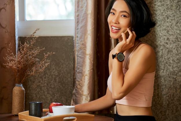 Schlanke schöne junge frau, die gesundes frühstück isst und mit ihrem fitnesstrainer oder freund telefoniert