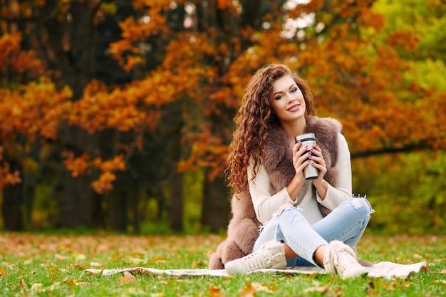 Schlanke schöne junge frau in einer pelzweste ruht im herbst im park und sitzt auf dem rasen auf dem rasen und trinkt tee aus einem thermocup