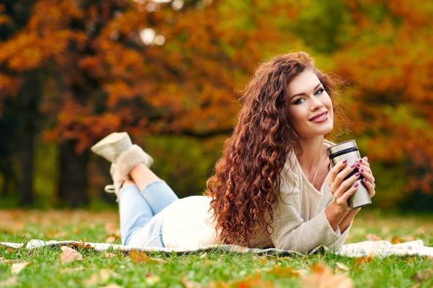 Schlanke schöne junge frau ruht im herbst im park und liegt auf dem rasen auf dem rasen und trinkt tee aus einem thermocup und lächelt