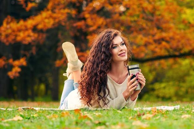 Schlanke schöne junge frau ruht im herbst im park und liegt auf dem rasen auf dem rasen und trinkt tee aus einem thermocup