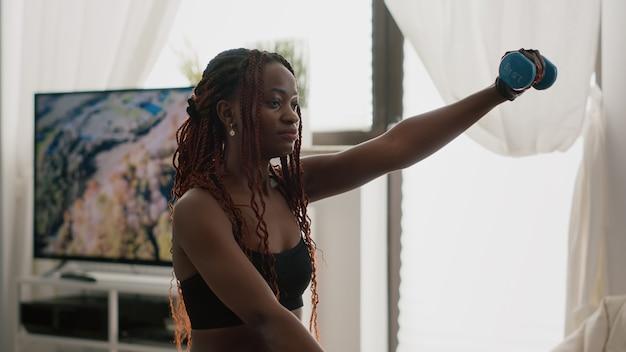 Schlanke schwarze trainerin mit training für körperübungen mit yoga-hanteln