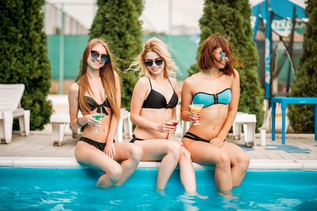 Schlanke sexy frauen in badeanzügen, die am pool sitzen