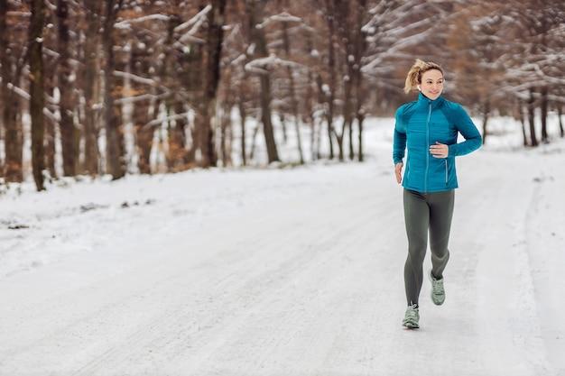 Schlanke sportlerin, die bei schneewetter im wald joggt. kaltes wetter, schnee, gesundes leben, fitness, gesunde gewohnheiten, natur