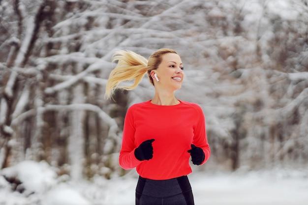 Schlanke sportlerin, die im wald am verschneiten wintertag läuft. winter fitness, schneewetter, gesundes leben
