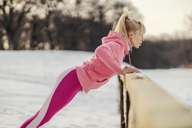Schlanke sportlerin, die liegestütze in der natur am verschneiten wintertag tut. winterfitness, schneewetter, kraft