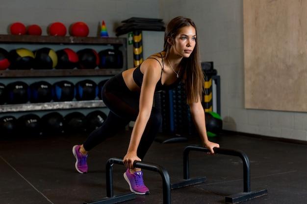 Schlanke sportlerin mit langen braunen haaren führt im fitnessstudio körperliche übungen durch und trägt farbige bälle. fotos für die werbung für sportgeräte oder kleidung.