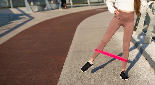 Schlanke sportliche frau, die morgens mit fitnessgummi an der brücke trainiert. leerer platz für text
