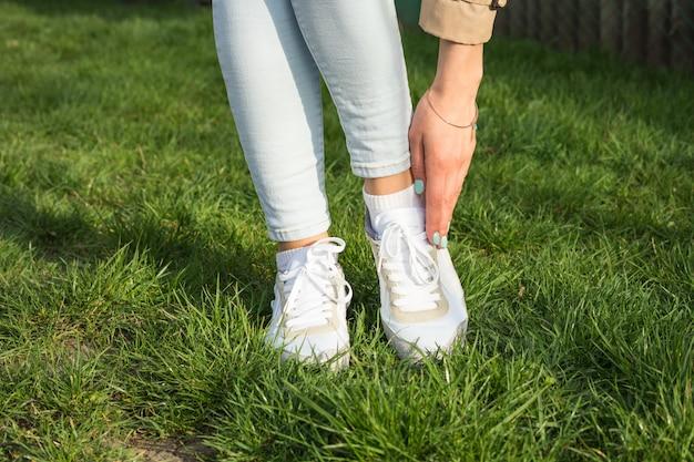 Schlanke weibliche beine in jeans und weißen turnschuhen auf einem grünen rasen an einem sonnigen tag