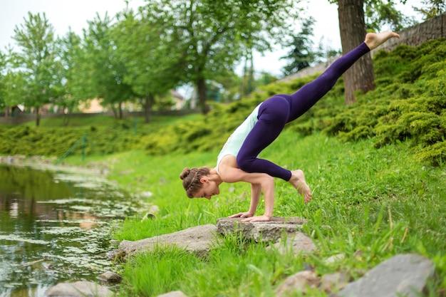 Schlanker junger brunettejogi führt komplexe yogaübung auf grünem gras im sommer durch