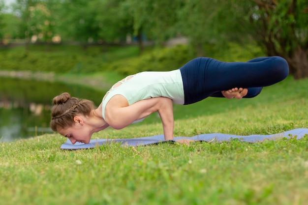Schlanker junger brunettejogi führt schwierige yogaübungen auf dem grünen gras im sommer durch