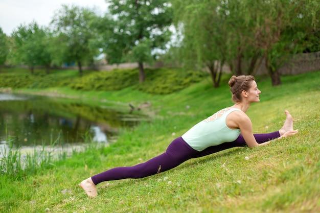 Schlanker junger brunettejogi führt schwierige yogaübungen auf dem grünen gras im sommer vor dem hintergrund der natur durch