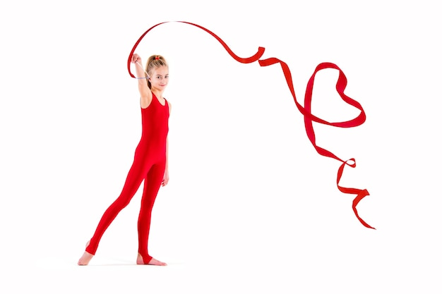 Schlanker turner im roten overall, der übungen mit band auf weißem hintergrund tut