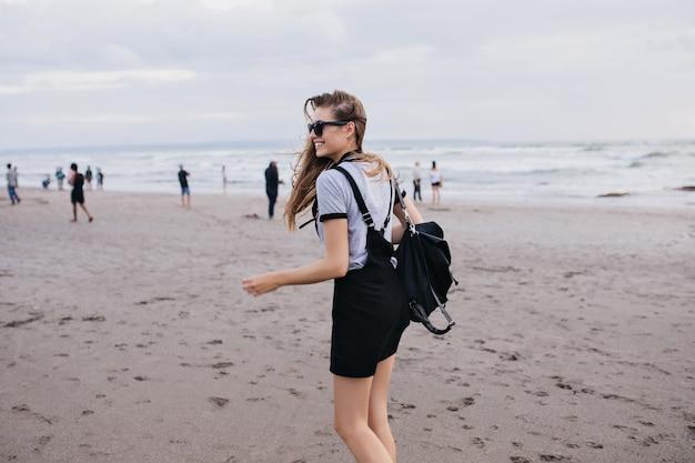 Schlankes blasses mädchen mit schwarzem rucksack, der mit glücklichem lächeln um strand geht. außenaufnahme der herrlichen dame, die spaß nahe meer in kaltem tag hat.