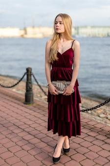 Schlankes blondes mädchen in elegantem knöchellangem burgunder-kleid, das weg auf dem damm schaut.