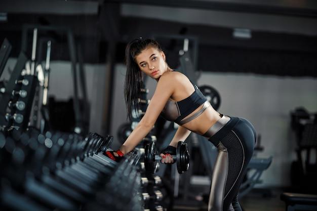 Schlankes, bodybuildermädchen, hebt den schweren dummkopf an, der vor dem spiegel beim training in der turnhalle steht. sportkonzept, fettverbrennung und gesunder lebensstil