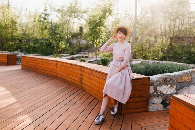 Schlankes elegantes mädchen mit altmodischem outfit, das im park auf erstaunlicher natur ruht
