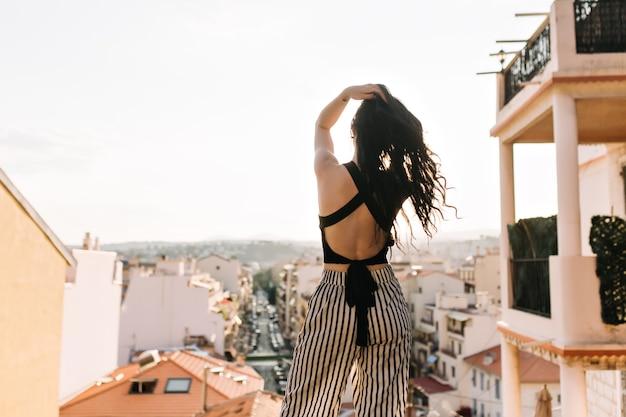 Schlankes elegantes mädchen mit langen dunklen haaren, die stadtblick von aussichtsplattform am morgen genießen