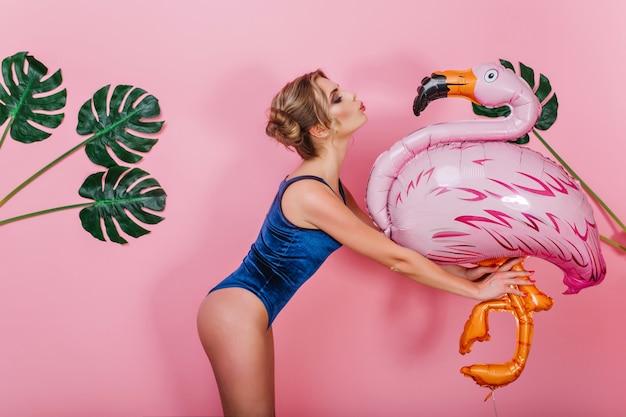 Schlankes erstaunliches mädchen im weinlesebodysuit, das großen spielzeugvogel küsst, der vor rosa wand steht. porträt der niedlichen formschönen jungen frau, die aufblasbaren flamingo hält und mit pflanzen auf hintergrund aufwirft