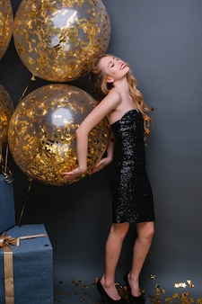 Schlankes europäisches mädchen trägt elegante schuhe, die mit partyballons tanzen und in ihrem geburtstag lächeln. innenfoto der kühlen blonden frau, die mit geschlossenen augen nahe geschenken steht.