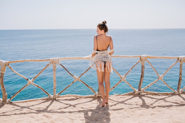 Schlankes gebräuntes mädchen mit niedlicher frisur in gestrickter kleidung, die auf terrasse steht und das meer betrachtet. erstaunliche junge frau, die meerblick in den sommerferien genießt und vor wasser aufwirft