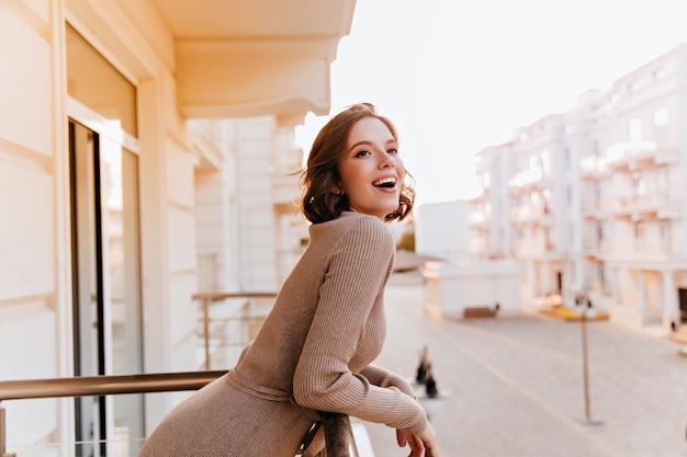 Schlankes gut gekleidetes mädchen, das stadt vom balkon betrachtet. attraktive sinnliche frau, die stadtblick genießt, während an der terrasse steht.