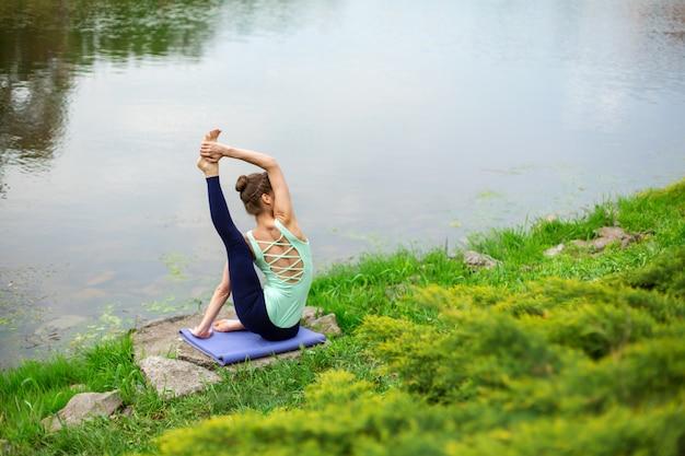 Schlankes kaukasisches brunettemädchen, das yoga im sommer auf einem grünen rasen durch den fluss tut