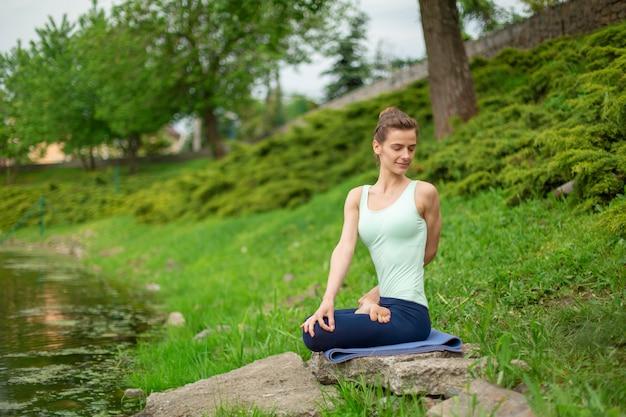 Schlankes kaukasisches brunettemädchen, das yoga im sommer auf einem grünen rasen tut