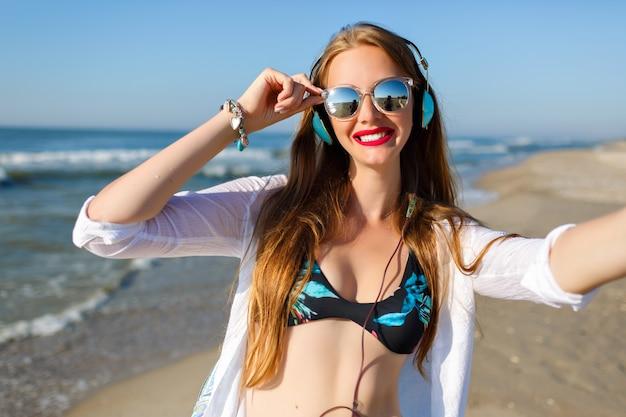 Schlankes langhaariges mädchen mit blasser haut, das selfie beim ausruhen im seebad macht. außenporträt der glücklichen dame in der sonnenbrille, die musik hört und meeresbrise am wochenende genießt.