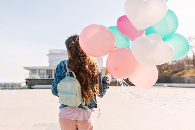 Schlankes mädchen, das jeansjacke und stilvolle hosen trägt, geht nach party entlang verlassener böschung. langhaarige frau mit niedlichem rucksack, der luftballons hält und warmen wind weht.