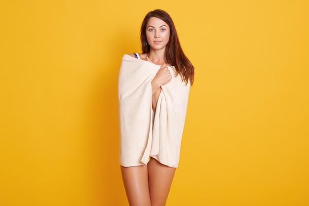 Schlankes mädchen eingewickelt in weißes handtuch isoliert auf gelb, weiblich mit dunklen langen haaren, modell mit perfekter haut. kopieren sie den platz für die werbung.