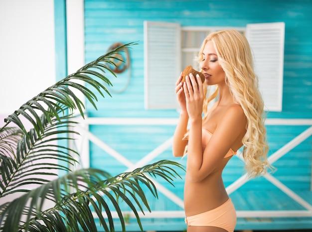 Schlankes mädchen im beige badeanzug hält kokosnuss in händen in der nähe ihres gesichts, augen geschlossen