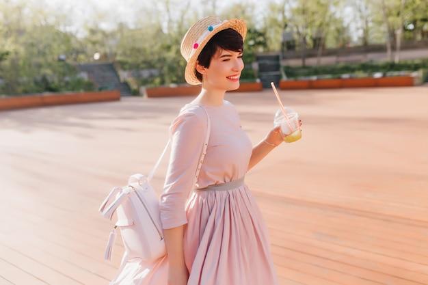 Schlankes mädchen im schönen langen kleid, das im park am sonnigen tag geht und leckeren cocktail mit lächeln trinkt