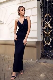 Schlankes mädchen im schwarzen abend dres, dünn, mode, frisur, glamourös, schuhe, outdoor, perfekter körper, blondine, schönheit, make-up, arme