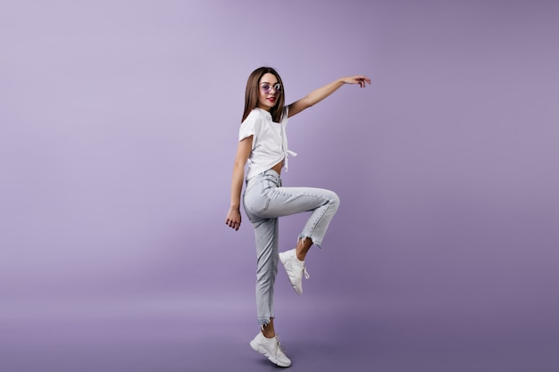 Schlankes mädchen in den niedlichen weißen turnschuhen, die auf einem bein aufwerfen. innenfoto der verträumten frau im jeans tanzen.
