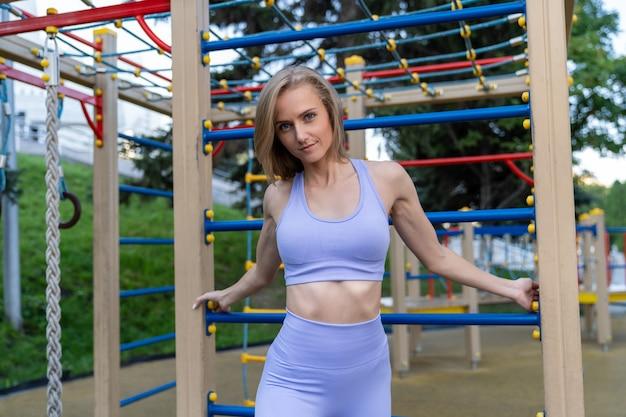 Schlankes mädchen in der fitnesskleidung, die auf dem straßensportplatz aufwirft