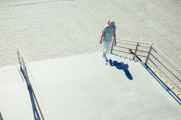 Schlankes mädchen in einer kappe und in jeans, die treppe in der stadt im sommer klettern