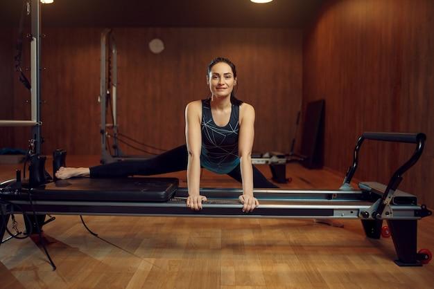 Schlankes mädchen in sportbekleidung, das den spagat macht, pilates-training auf trainingsgerät im fitnessstudio.