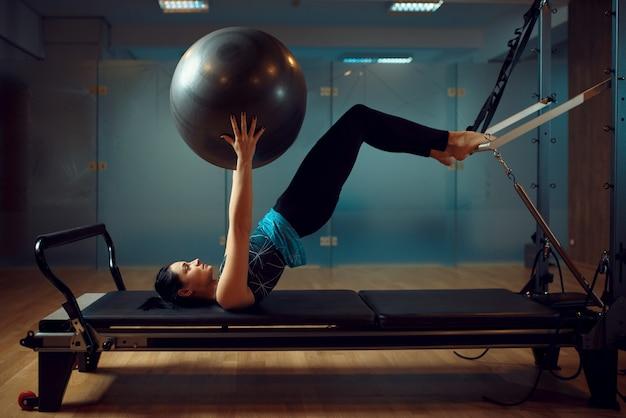 Schlankes mädchen in sportbekleidung, pilates-training mit ball auf übungsmaschine im fitnessstudio.