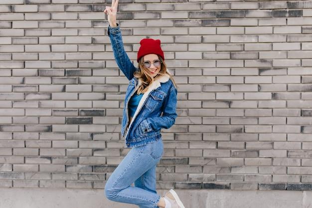 Schlankes mädchen in trendigen jeans, die spaß auf der straße am kalten frühlingstag haben. glückseliges weibliches modell in der jeanskleidung, die auf stadtmauer tanzt und hände winkt.