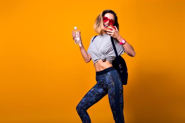 Schlankes mädchen mit kurzen haaren mit rucksack, der ins fitnessstudio geht und eine flasche wasser hält. lachende sportliche junge frau in der sonnenbrille, die auf hellem hintergrund im studio mit apfel in der hand aufwirft.