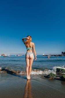 Schlankes mädchen mit sexy arsch im badeanzug steht im urlaub am strand am meer