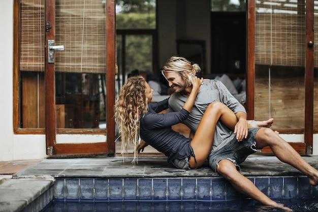 Schlankes mädchen umarmt ihren geliebten freund und sieht ihn mit liebe an. mann und frau entspannen am pool