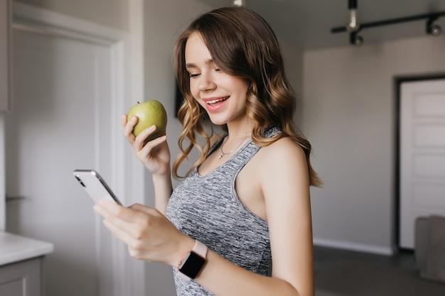 Schlankes reizendes mädchen mit smartphone am morgen. innenporträt der atemberaubenden dunkelhaarigen frau, die grünen apfel isst und lächelt.
