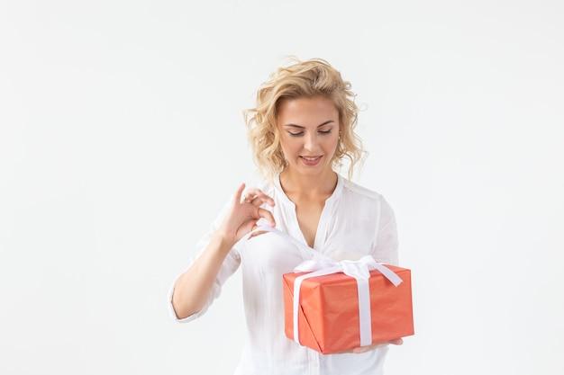 Schlankes schönes junges blondes mädchen, das eine rote geschenkbox in ihren händen hält, während gegen eine weiße wand steht. konzept von aktien, feiertagen und boni.