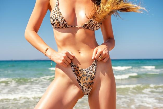 Schlankes sexy mädchen mit einer perfekten figur in einem leopardenbikini am strand