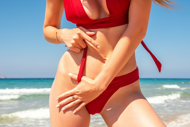 Schlankes sexy mädchen mit einer perfekten figur in einem roten bikini am strand